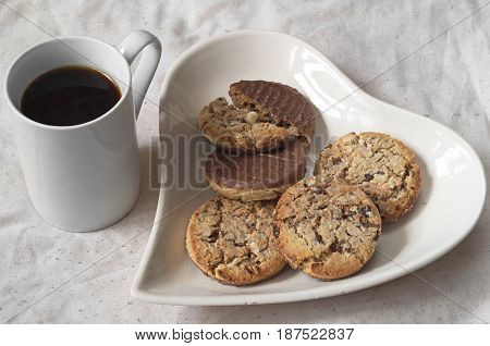 Plate in the shape of heart with chocolate cookies and black coffee for breakfast
