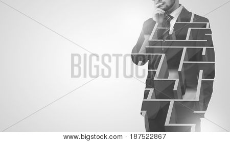 Young businessman in suit standing with maze graphic