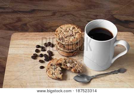 Cup of coffee and cookies with chocolate on wooden board for breakfast