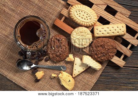 Cup of hot coffee and different shortbread cookies on old wooden background top view