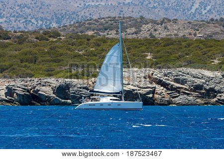 CRETE GREECE - JULY 11 2016: The yacht with tourists on the sea. View from the sea on the north coast of Crete.
