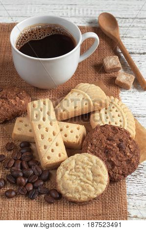 Cup of coffee and different cookies on white wooden table