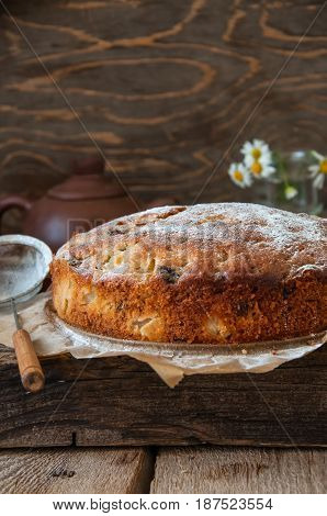 Freshly Baked Homemade Cake With Pear And Raisin Sprinkled With Powdered Sugar On A Wooden Backgroun