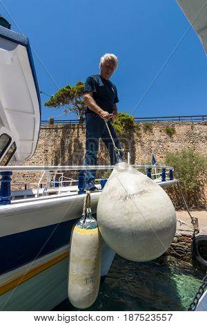 CRETE GREECE - JULY 11 2016: A man is moored pleasure ship.