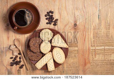 Cup of hot coffee and different cookies on old wooden table top view. Space for text