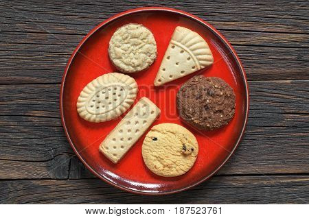 Different shortbread cookies in red plate on dark wooden background top view