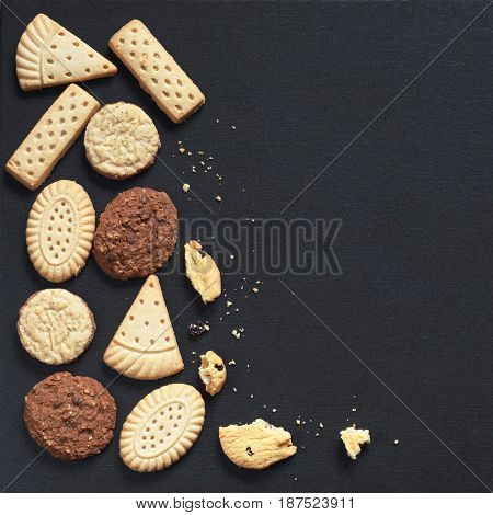 Mix of shortbread cookies on black stone background top view. Space for text