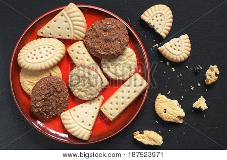 Different shortbread cookies in red plate on black stone background top view