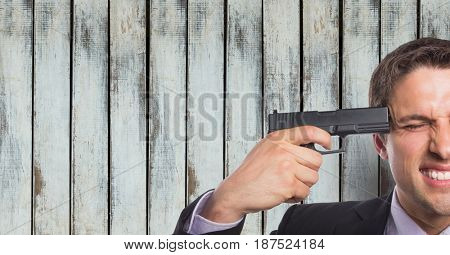 Digital composite of Businessman shooting himself against wooden wall