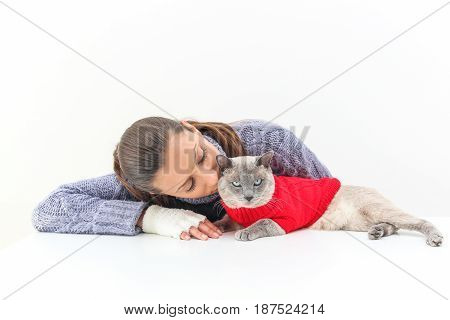 A Woman Wears A Purple Sweater And White Gloves With A Siamese Cat Wearing A Red Sweater