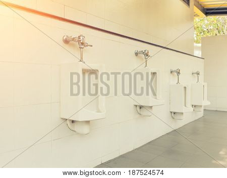 Row of white urinal for men on tile wall in toilet.