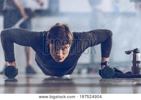 athletic young sportsman doing push ups with dumbbells at the gym gym workout concept