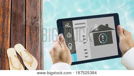 Digital composite of Hands using smart home app at poolside