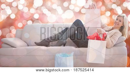 Digital composite of Happy woman with shopping bags lying on sofa over bokeh