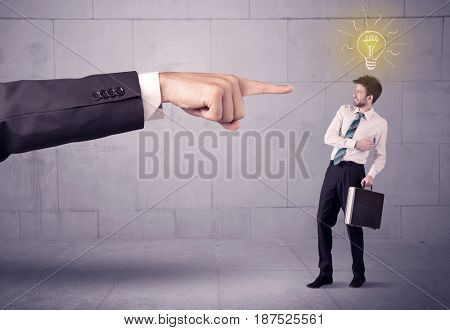 A huge ordering hand pointing at scared and confused businessman with a good idea illustrated by a drawn glowing light bulb concept