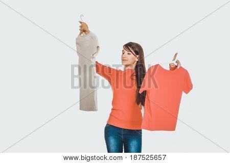 Young woman choosing shirt.