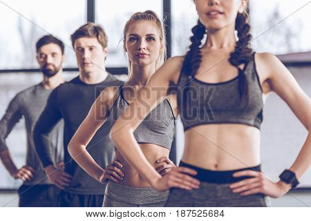Group Of Athletic Young People In Sportswear Exercising At The Gym