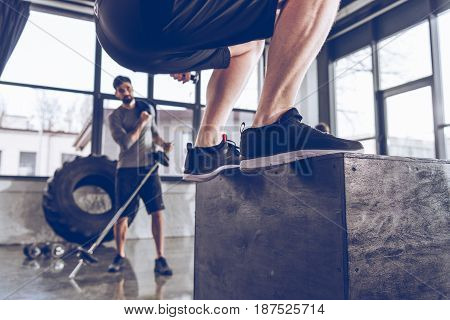 Close-up partial view of sporty people exercising at cross fit gym workout