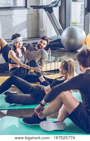 Smiling Young Sporty People Lying On Yoga Mats And Talking While Exercising At The Gym
