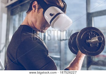 Side View Of Man In Virtual Reality Headset Exercising With Dumbbell In Gym