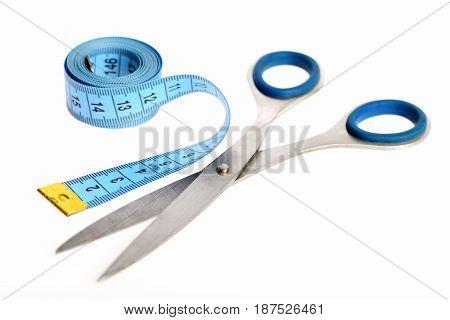 Roll Of Blue Measure Tape Lying Beside Silver Scissors
