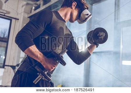 side view of man in virtual reality headset exercising with dumbbells in gym