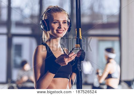 portrait of smiling woman listening music in headphones near trx equipment in gym