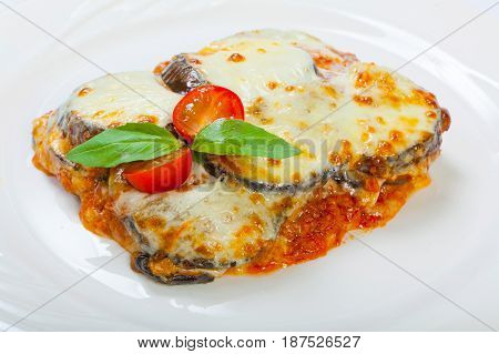 Baked Eggplant With Cheese, Tomatoes And Spices On A White Plate. A Dish Of Eggplant Is On A Wooden