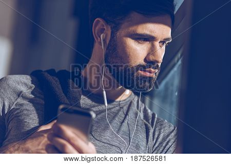 Portrait Of Man Listening Music In Earphones And Looking Out Window