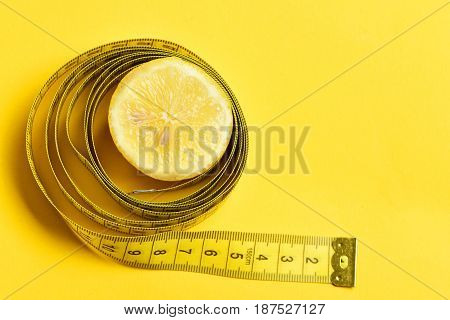 Slice Of Lemon With Measuring Tape On Yellow