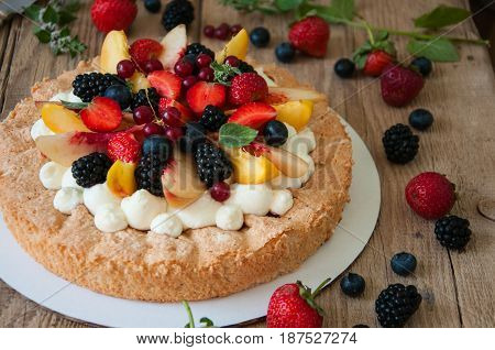Homemade Dacquoise Cake With Wipped Cream Cheese Garnished With Summer Berries And Peaches, Close Up