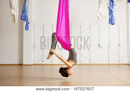 Inversion bow pose in aero anti gravity yoga. Aerial yoga exercise made with help of pink hammock. Young girl in grey sport suit does trainings