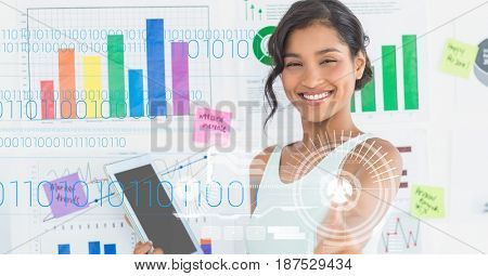 Digital composite of Happy businesswoman holding digital tablet against graphs