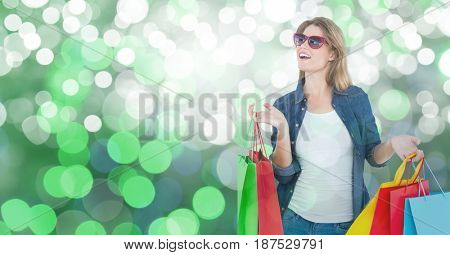 Digital composite of Surprised woman with carrying shopping bags over bokeh