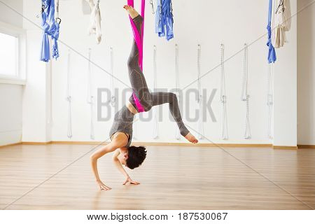 Inversion locust pose in aero anti gravity yoga. Woman hangs upside down. Aerial yoga exercise made with help of pink hammock. Young girl in grey sport suit does trainings