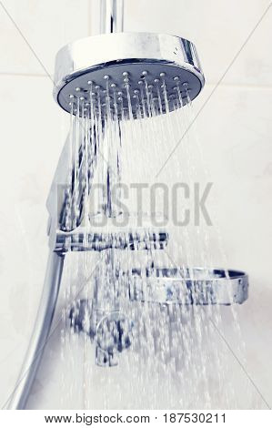 Shower head with water. Color toning applied.
