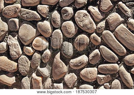 Natural cobblestones background. Abstract texture. Paved pathway.