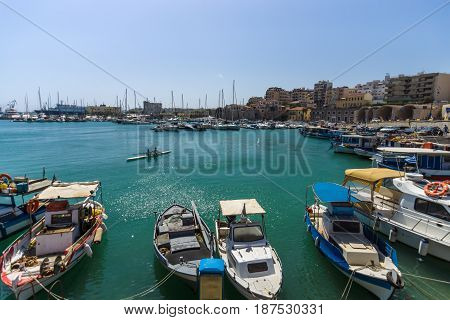 HERAKLION GREECE - JULY 16 2016: Crete. Moored fishing boats in the seaport. In the background the city's neighborhoods.