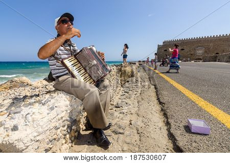 HERAKLION GREECE - JULY 16 2016: Crete. Musician on the waterfront plays accordion. In the background Venetian fortress.
