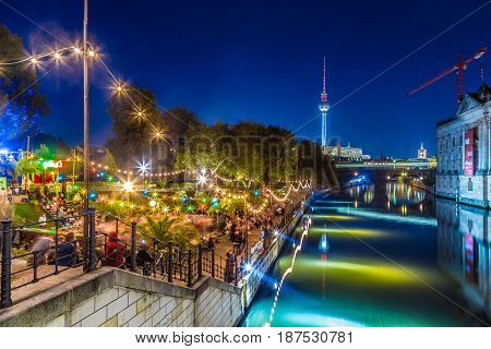 People dancing at summer Strandbar beach party near Spree river at Museum Island with famous TV tower in the background at night Berlin Germany