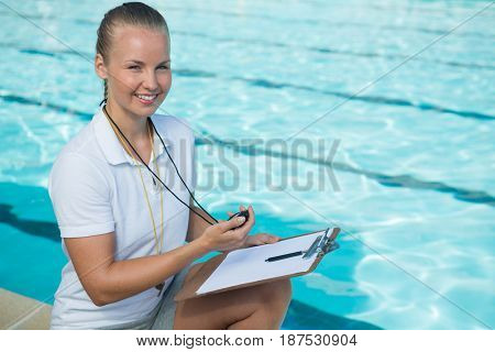 Portrait of smiling swim coach holding clipboard and stopwatch at poolside
