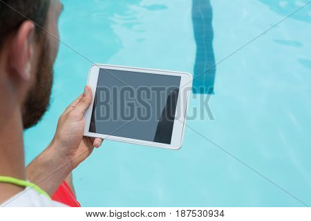 Rear view of lifeguard using digital tablet at poolside