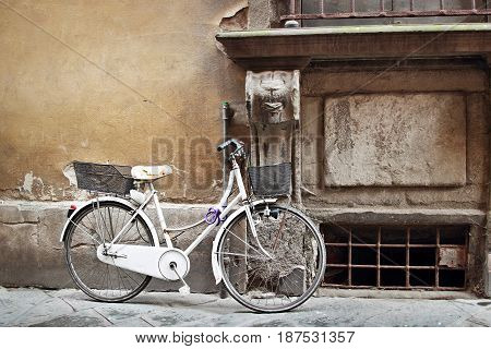 White retro bicycle with basket at the street of old town Italy. Aged wall of medieval house. Bicycle is popular transport in Italy.