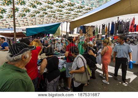 HERAKLION GREECE - JULY 16 2016: Crete. Popular among residents and tourists gypsy market. Barker advertise their goods.