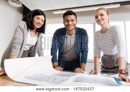 Great mood. Joyful happy professional engineers standing at the table and looking at you while being in a great mood