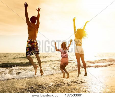 happy Family jumping on the beach at sunset
