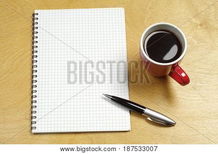 Cup of coffee and notepad on a wooden table
