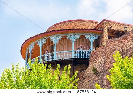 Tbilisi, Georgia - April 29, 2017: People at the old traditional wooden carving balcony in Old Town of Tbilisi, Georgia