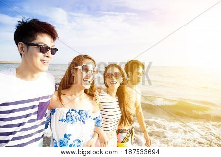 happy young group walking on the beach