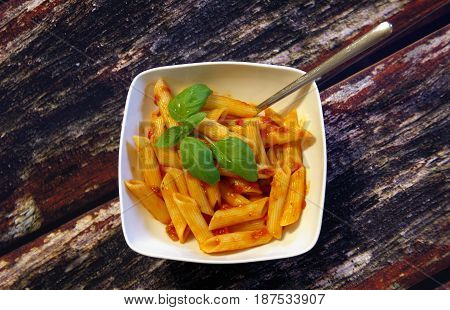A plate of penne pasta with tomato sauce on wooden table
